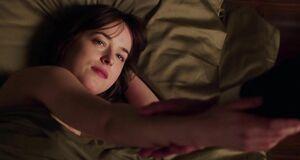 Дакота Джонсон лежит без лифчика в постели